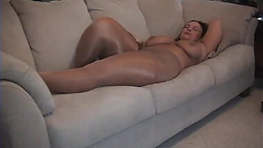 Belle relaxing on couch with Shiny Pantyhose